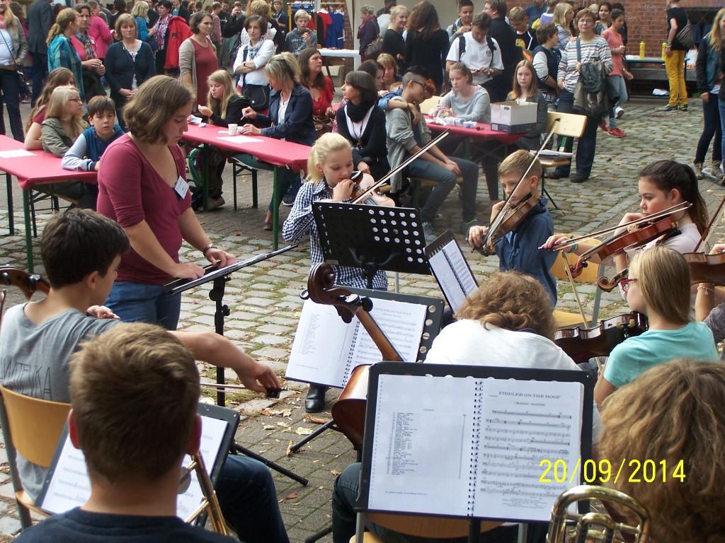 Schüler, Eltern und Lehrer feiern und lassen sich musikalisch unterhalten.